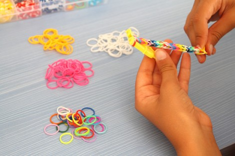 Child's hands doing bracelet with colorful rubber bands